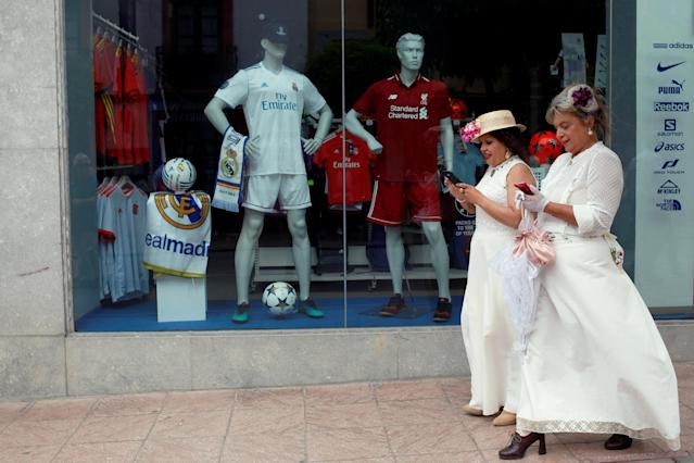 "Women, dressed as bourgeoises, use their mobile phones while they walk past a showcase with mannequins displaying the Real Madrid soccer jersey and the Liverpool soccer jersey, before the Champions League Final, as they participate in the sixth edition of ""Ronda Romantica"" (Romantic Ronda) in Ronda, southern Spain, May 26, 2018. REUTERS/Jon Nazca"