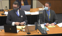 In this image from video, defense attorney Eric Nelson, left, and defendant, former Minneapolis police officer Derek Chauvin, right, listen, Wednesday, April 14, 2021, as Hennepin County Judge Peter Cahill presides over motions in the trial of Chauvin at the Hennepin County Courthouse in Minneapolis. Chauvin is charged in the May 25, 2020 death of George Floyd. (Court TV, via AP, Pool)