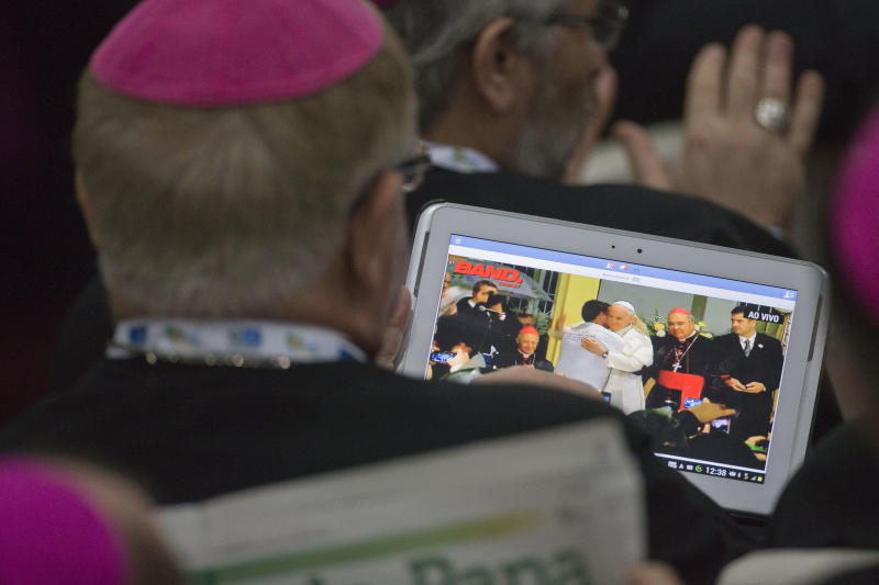 A bishop watches live video on his tablet of Pope Francis at an event as he waits for Francis to arrive for a meeting with Brazilian cardinals and bishops at St Joaquim Palace in Rio de Janeiro, Saturday, July 27, 2013. Pope Francis took his message to shake up the Catholic Church to bishops from around the world on Saturday, challenging them to get out of their churches and go to the farthest margins of society to find the faithful and preach. (AP Photo/Domenico Stinellis)