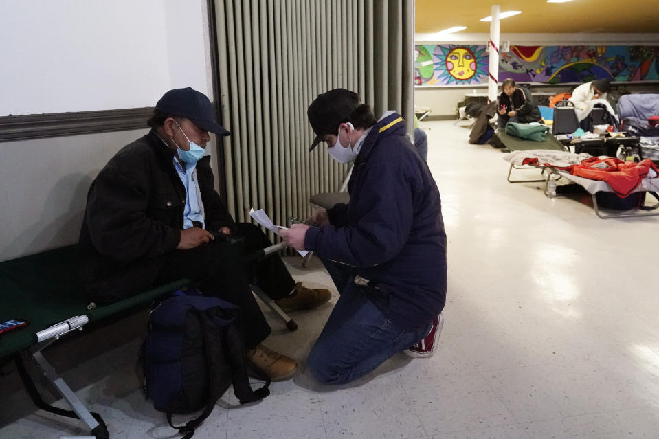 Pastor Gavin Rogers, right, works with Alberto, left, who was moved to a warming shelter to escape sub-freezing temperatures at Travis Park Methodist Church, Tuesday, Feb. 16, 2021, in San Antonio. (AP Photo/Eric Gay)