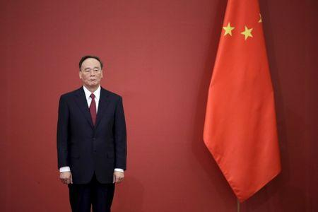FILE PHOTO: China's Politburo Standing Committee member Wang Qishan, the head of China's anti-corruption watchdog, stands next to a Chinese flag during a medal ceremony marking the 70th anniversary of the Victory of Chinese People's War of Resistance Against Japanese Aggression, for World War Two veterans, at the Great Hall of the People in Beijing, China, September 2, 2015.  REUTERS/Jason Lee