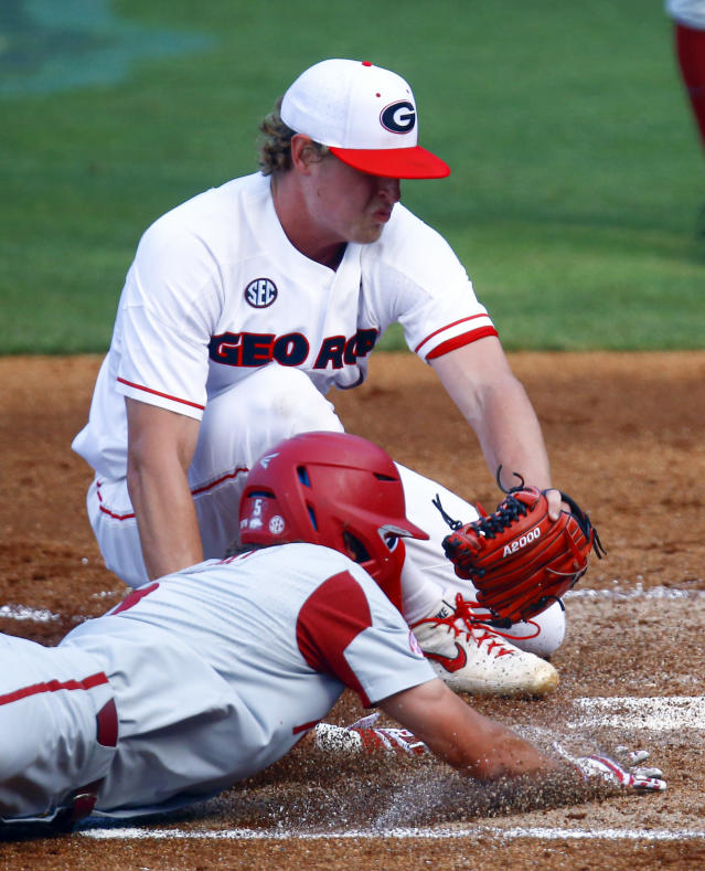 Arkansas' Jacob Nesbit beats the tag from Georgia pitcher Cole Wilcox as he slides into home during the third inning of a Southeastern Conference tournament NCAA college baseball game Thursday, May 23, 2019, in Hoover, Ala. (AP Photo/Butch Dill)