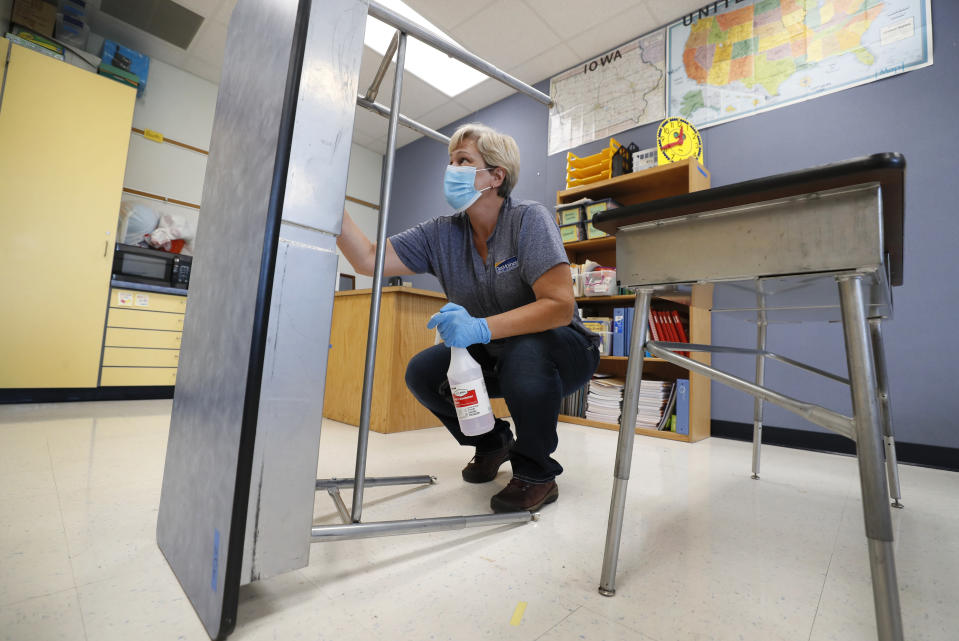 Des Moines Public Schools custodian Cynthia Adams cleans a desk in a classroom at Brubaker Elementary School, Wednesday, July 8, 2020, in Des Moines, Iowa. As the Trump administration pushes full steam ahead to force schools to resume in-person education, public health experts warn that a one-size-fits-all reopening could drive infection and death rates even higher. (AP Photo/Charlie Neibergall)