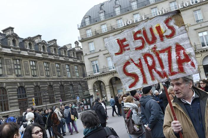 """A protester holds a placard reading """"I am Syriza"""" during a demonstration in support of the Greek people on February 15, 2015 in Paris (AFP Photo/Loic Venance)"""