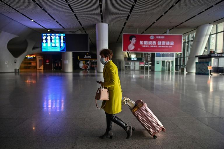 Travellers are allowed to leave Wuhan train station after showing a green code on a mobile app to prove they are healthy (AFP Photo/Hector RETAMAL)