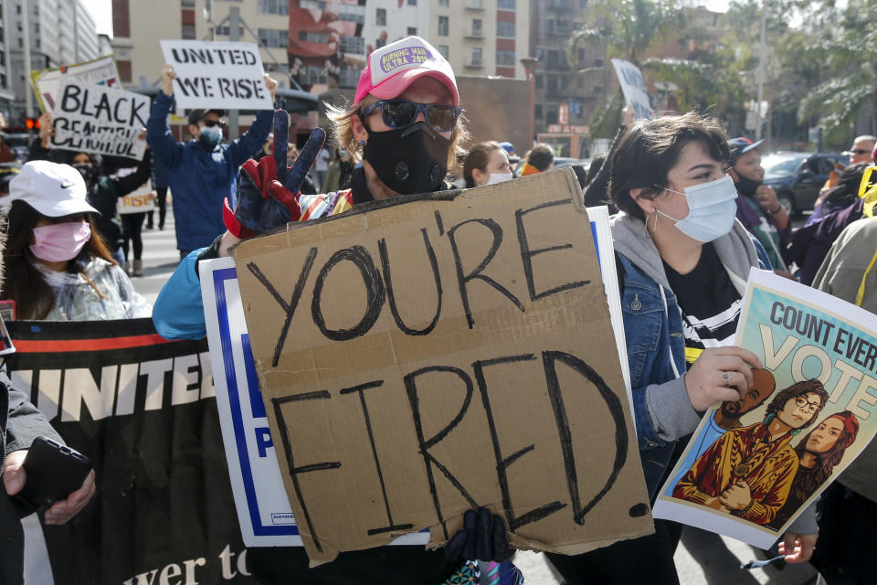 A person celebrating in the streets of Los Angeles holds a sign saying 'you're fired', in reference to Donald Trump's catchphrase.
