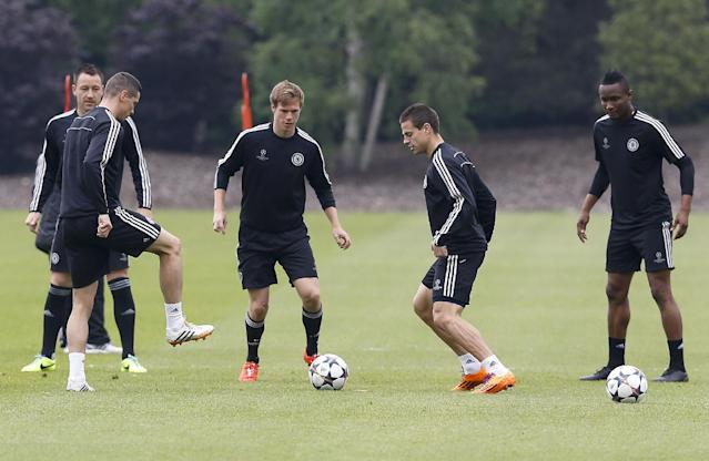 Chelsea players kick a ball during a training session at Cobham in England Tuesday, April 29, 2014. Chelsea will play a Champions League semifinal second leg soccer match against Atletico Madrid on Wednesday. (AP Photo/Kirsty Wigglesworth)
