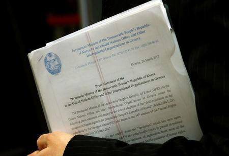 Mun Jong Chol, counselor at the North Korea mission to the U.N. in Geneva, holds copies of a press release aside of a meeting of the Human Rights Council at the United Nations in Geneva, Switzerland March 24, 2017. REUTERS/Denis Balibouse