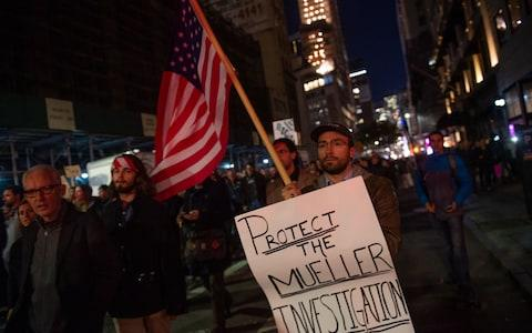People protest and march against US President Donald Trump's alleged interference in Robert Mueller's investigation in New York City - Credit: AFP