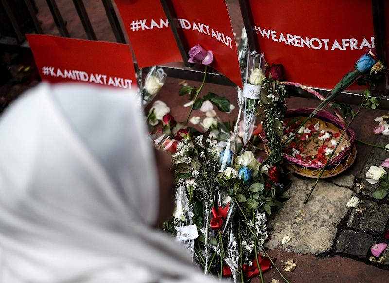 A woman offers flowers during a vigil outside the damaged Starbucks coffee shop in Jakarta on January 15, 2016, a day after a series of explosions hit the Indonesian capital