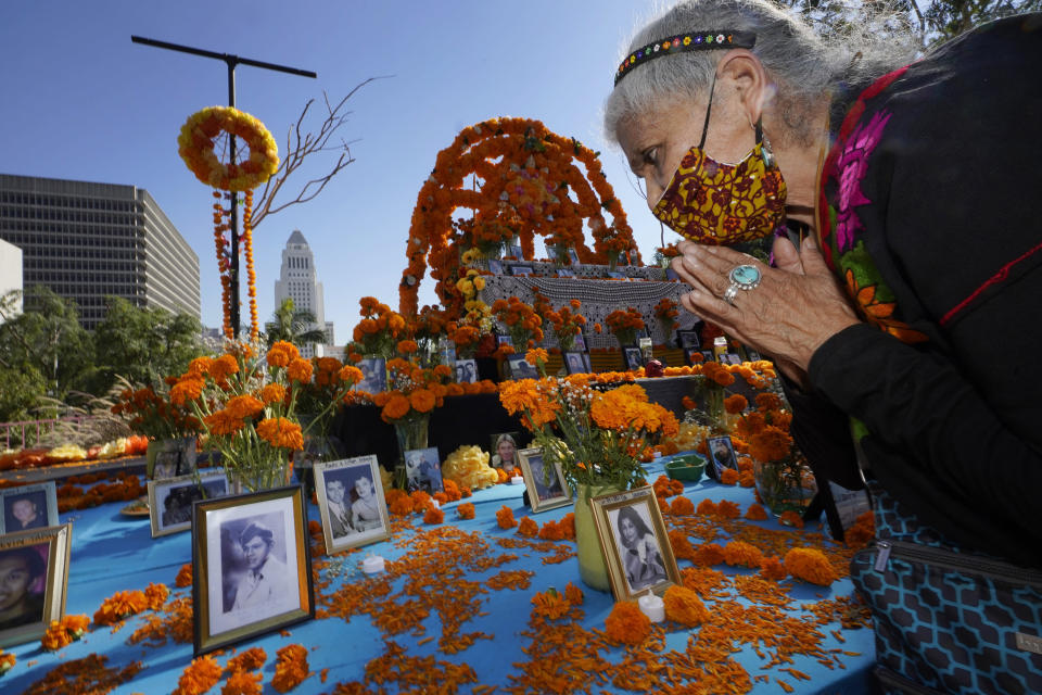 "Ofelia Esparza, 88, from East Los Angles, has brough fresh marigolds, often called ""flowers of the dead,"" and placed them next to pictures of family members who died in 2020, at an altar for Day of the Dead, titled ""2020 Memorial to Our Resilience,"" at Grand Park in Los Angeles, Thursday, Oct. 29, 2020. Day of the Dead, or Dia de los Muertos, the annual Mexican tradition of reminiscing about departed loved ones with colorful altars, or ofrendas, is typically celebrated Sunday through Monday. It will undoubtedly be harder for Latino families in the U.S. torn apart by the coronavirus. (AP Photo/Damian Dovarganes)"