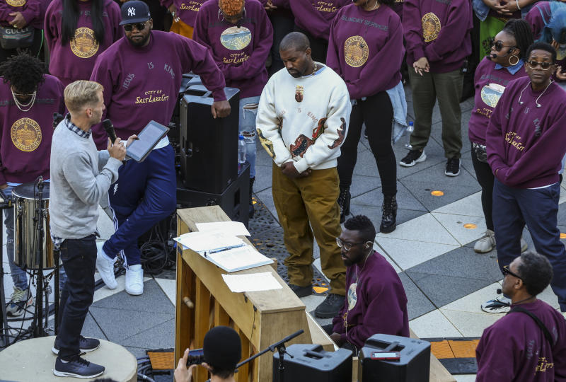 "Kanye West, centro, durante una oración en su ""Sunday Service"" en The Gateway en Salt Lake City el sábado 5 de octubre de 2019. Miles de personas llegaron para ver a West en su misa-concierto. (Colter Peterson/The Deseret News via AP)"