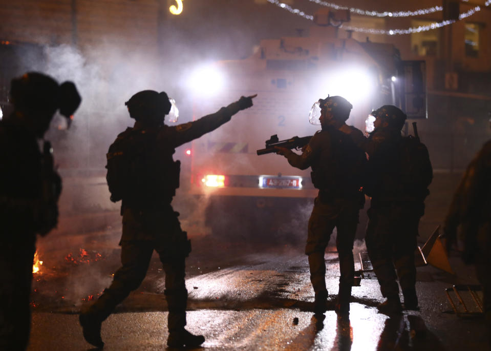 Israeli police officers fire stun grenades toward Palestinian demonstrators during clashes at Damascus Gate just outside Jerusalem's Old City, Saturday, May 8, 2021. (AP Photo/Oded Balilty)