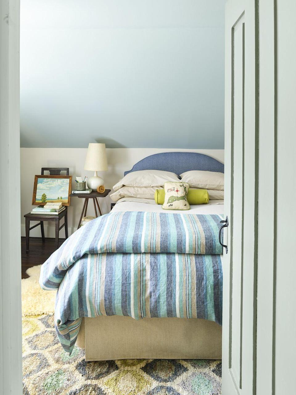 """<p>To visually open up his oddly configured bedroom, homeowner—and <em>Country Living</em> photo stylist—Matthew Gleason looked for colors right outside his window, starting with the blue sky. To emphasize its slope and height, he used the pretty soft blue on the ceiling and then chose a contrasting white for the short walls. He continued the blue thread with an upholstered headboard and striped linens. Keeping everything in the same blue family but of varying hues keeps it more active and fun. </p><p><strong>Get the Look: </strong><br>Ceiling Paint Color: <a href=""""https://store.benjaminmoore.com/storefront/index.ep"""" rel=""""nofollow noopener"""" target=""""_blank"""" data-ylk=""""slk:Fantasy Blue by Benjamin Moore"""" class=""""link rapid-noclick-resp"""">Fantasy Blue by Benjamin Moore </a></p>"""