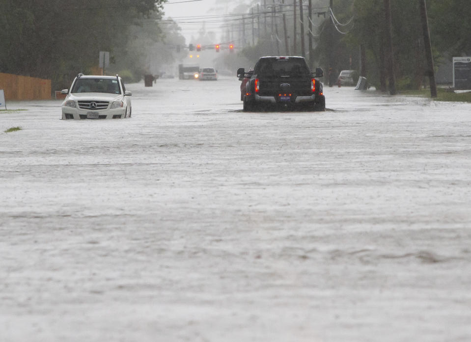 Cars sit stalled on a flooded Sale Road during heavy rains in Lake Charles, La., Monday, May 17, 2021. (Rick Hickman/American Press via AP)