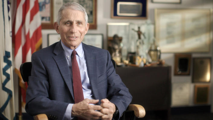 Dr. Anthony Fauci wears a blue suit and dark red tie while sitting in an office in front of plaques, picture frames and an American flag.