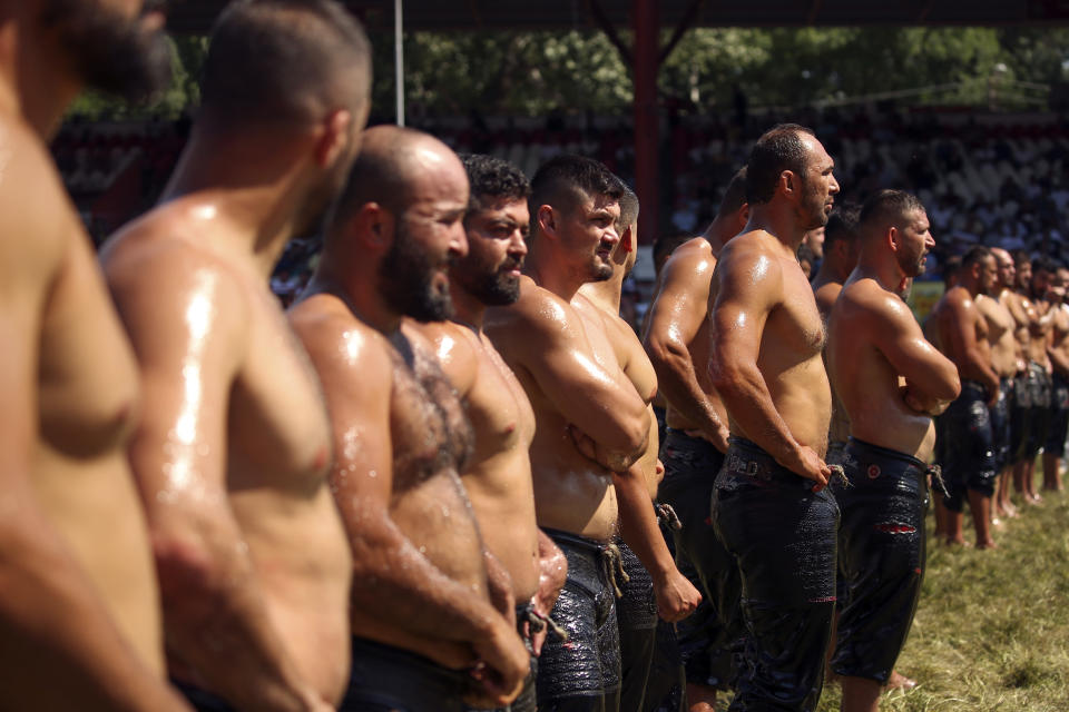 Wrestlers, doused in olive oil, are introduced to the crowds during the 660th instalment of the annual Historic Kirkpinar Oil Wrestling championship, in Edirne, northwestern Turkey, Saturday, July 10, 2021.Thousands of Turkish wrestling fans flocked to the country's Greek border province to watch the championship of the sport that dates to the 14th century, after last year's contest was cancelled due to the coronavirus pandemic. The festival, one of the world's oldest wrestling events, was listed as an intangible cultural heritage event by UNESCO in 2010. (AP Photo/Emrah Gurel)