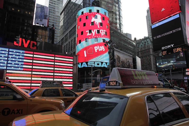 FILE - In this Dec. 16, 2011 file photo, the corporate logo for Zynga, center, is shown on an electronic billboard at the Nasdaq MarketSite, in New York. Zynga Inc., releases quarterly financial results Tuesday, Feb. 14, 2012, after the market close.  (AP Photo/Mark Lennihan, File)