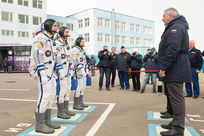 Expedition 63 crew members Chris Cassidy of NASA, left, and Anatoly Ivanishin and Ivan Vagner of Roscosmos report to Roscosmos Director General Dmitry Rogozin, right, as they depart building 254 for the launch pad, Thursday, April 9, 2020 at the Baikonur Cosmodrome in Kazakhstan.