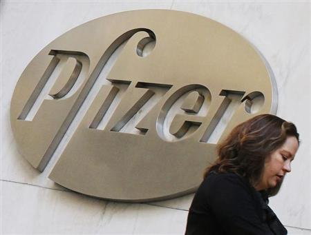 A woman walks past the Pfizer Inc. headquarters in New York