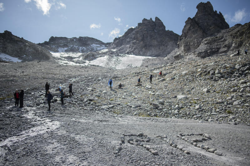 The letters 'RIP' (rest in peace) are written with stones during a commemoration in front of the 'dying' glacier of Pizol mountain in Wangs, Switzerland, Sunday, Sept. 22, 2019. Various organizations gathered to shine a light on climate change and melting glaciers. (Gian Ehrenzeller/Keystone via AP)
