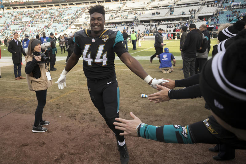 Jacksonville Jaguars outside linebacker Myles Jack (44) celebrate in the tunnel with fans at the end of an NFL wild-card playoff football game against the Buffalo Bills, Sunday, Jan. 7, 2018, in Jacksonville, Fla. Jaguars beat the Bills 10-3. (AP Photo/Stephen B. Morton)