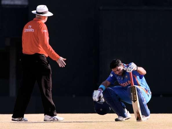 CHENNAI, INDIA - MARCH 20: Yuvraj Singh of India suffering from the heat is attended by umpire Steve Davis during the Group B ICC World Cup match between India and West Indies at M. A. Chidambaram Stadium on March 20, 2011 in Chennai, India. (Photo by Graham Crouch/Getty Images)