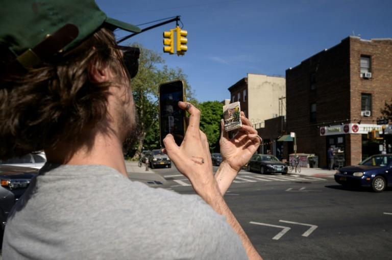 Artist Steve Wasterval takes a photo of his mini landscape in Greenpoint, New York on May 25, 2021. He will post it on Instagram to let followers know that a new hunt has begun