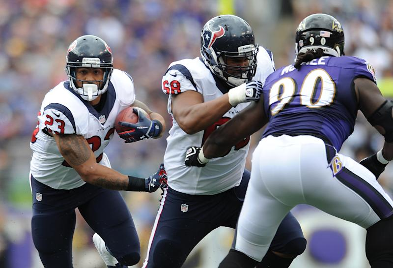 Houston Texans running back Arian Foster, left, rushes the ball as teammate Ryan Harris, center, blocks Baltimore Ravens linebacker Pernell McPhee in the first half of an NFL football game Sunday, Sept. 22, 2013, in Baltimore. (AP Photo/Gail Burton)