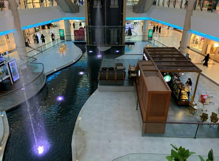 People spend time at a mall near a closed food court in the Saudi capital Riyadh, on February 5, 2021