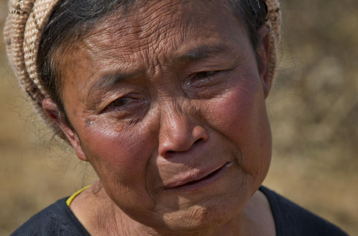 In this Jan 28 photo, Daw Li weeps before the graves of her two oldest sons, both victims of heroin overdoses, at Nampatka village cemetery, northeastern Shan State, Myanmar. In this village, roughly half the population uses heroin and opium. Residents once hoped new political and economic reforms sweeping their country would bring change to the wild hinterlands. Instead, many say their lives have only gotten worse as local authorities' complicity and neglect have enabled a spiraling drug trade. (AP Photo/Gemunu Amarasinghe)