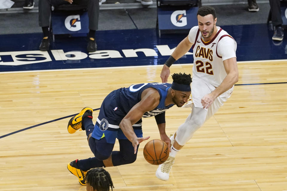 Minnesota Timberwolves' Josh Okogie, left, drives around Cleveland Cavaliers' Larry Nance Jr. (22) in the first half of an NBA basketball game Sunday, Jan. 31, 2021, in Minneapolis. (AP Photo/Jim Mone)