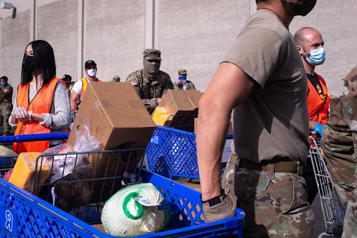 Volunteers and Arizona Army National Guard members wait with loaded carts Nov. 23 during the holiday food distribution at St. Mary's Food Bank in Phoenix.