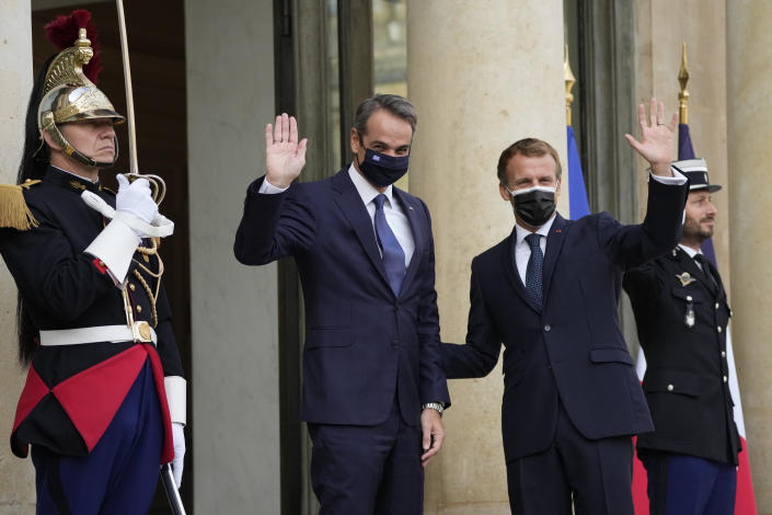 French President Emmanuel Macron and Prime Minister Kyriakos Mitsotakis, center, wave Tuesday, Sept. 28, 2021 at the Elysee Palace in Paris. The leaders of Greece and France are expected to announce a major, multibillion-euro deal in Paris on Tuesday involving the acquisition by Greece of at least six French-built warships, Greek state ERT TV reported. (AP Photo/Francois Mori)