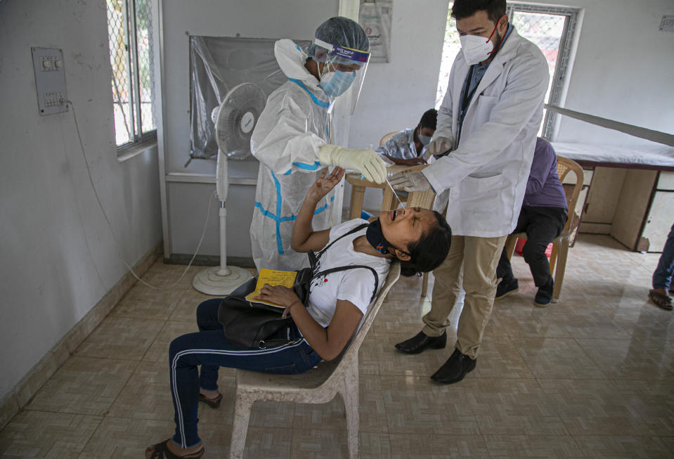 A health worker takes a nasal swab sample of a girl to test for COVID-19 during a random test for the family members of army personnel at the army base hospital in Gauhati, India, Monday, Oct. 19, 2020. (AP Photo/Anupam Nath)