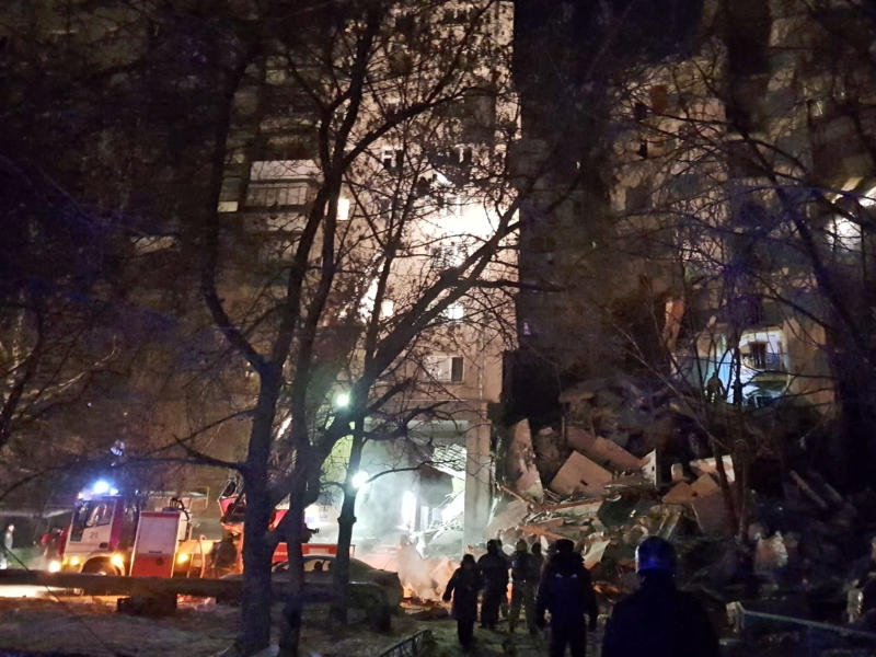 This photo provided by www.verstov.info shows Emergency Situations employees working at the scene of a collapsed apartment building in Magnitogorsk, a city of 400,000 people, about 1,400 kilometers (870 miles) southeast of Moscow, Russia, Monday, Dec. 31, 2018. Russian emergency officials say that at least four people have died after sections of the apartment building collapsed after an apparent gas explosion in the Ural Mountains region. (verstov.ru photo via AP)