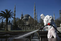 FILE - In this Saturday, March 21, 2020, file photo, a municipality worker wearing a face mask and protective suit disinfects the area outside the historical Sultan Ahmed Mosque, also known as Blue Mosque, amid the coronavirus outbreak, in Istanbul. When Turkey changed the way it reports daily COVID-19 infections, it confirmed what medical groups and opposition parties have long suspected — that the country is faced with an alarming surge of cases that is fast exhausting the Turkish health system. The official daily COVID-19 deaths have also steadily risen to record numbers in a reversal of fortune for the country that had been praised for managing to keep fatalities low. With the new data, the country jumped from being one of the least-affected countries in Europe to one of the worst-hit.(AP Photo/Emrah Gurel, File)