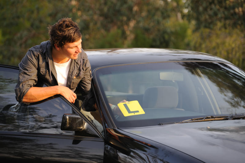 A young man looks stands outside his car with the front door open. A learner plate is on the windshield.