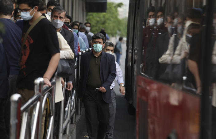 Commuters leave a bus stop in downtown Tehran, Iran, Tuesday, May 11, 2021. (AP Photo/Vahid Salemi)
