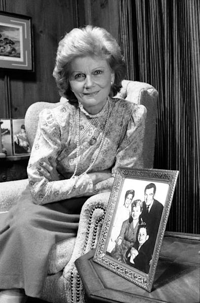 """FILE - In this Sept. 22, 1986 file photo, actress Barbara Billingsley poses next to a portrait of her television family, Hugh Beaumont, Tony Dow, Jerry Mathers and herself as the Cleaver family from """"Leave It To Beaver."""" Why settle for one great mom when, as any TV viewer knows, you can adopt a series of them? AP Television Writer Lynn Elber chooses five of the best sit com moms, from the demure 1950s version, such as the role of June Cleaver played by Barbara Billingsley, to the freewheeling 21st-century incarnation. (AP Photo/Doug C. Pizac, File)"""