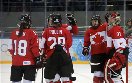 Canada's Catherine Ward, Marie-Philip Poulin, Jocelyne Larocque and goalie Charline Labonte celebrate after defeating Team USA in their women's preliminary round hockey game at the Sochi 2014 Winter Olympic Games February 12, 2014 REUTERS/Mark Blinch
