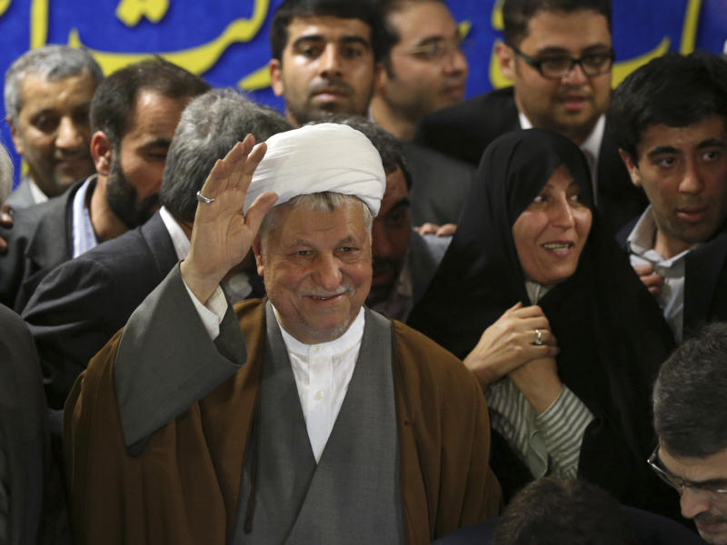 In this Saturday, May 11, 2013 photo, former President Akbar Hashemi Rafsanjani, waves to media, as he registers his candidacy for the upcoming presidential election, while his daughter Fatemeh, smiles at second right, at the election headquarters of the interior ministry in Tehran, Iran. On Saturday Rafsanjani's made a last minute surprise decision to enter Iran's presidential election process, which now includes more than 680 hopefuls and will culminate June 14 with just a handful of names on the ballot to succeed Mahmoud Ahmadinejad. In one of his first statements since joining the race, Rafsanjani spoke in general terms Sunday of seeking a new ``economic and political'' rebirth in a time of ``foreign threats and sanctions.'' (AP Photo/Ebrahim Noroozi)