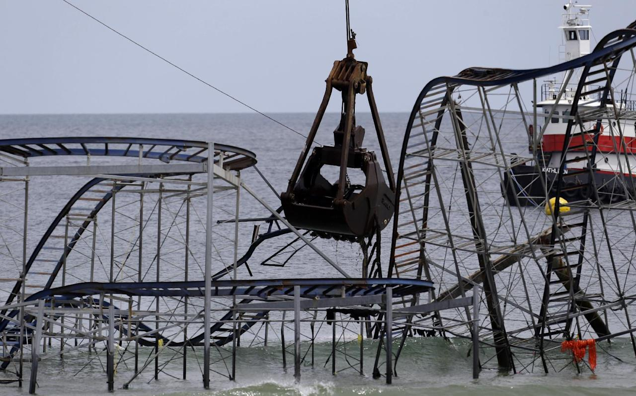 The claw of a crane, center, tears through the structure of the Jet Star Roller Coaster, Tuesday, May 14, 2013, in Seaside Heights, N.J. Workers began to demolish the roller coaster, which fell in the ocean when part of the Casino Pier was washed away by Superstorm Sandy in October. (AP Photo/Julio Cortez)