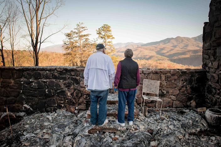 <p>DEC. 1, 2016 — Richard T. Ramsey and Sue Ramsey hold hands while looking at the skyline from the remains of their house of 41 years in Gatlinburg, Tenn. They safely evacuated from their home as wildfire approached Monday evening. (Andrew Nelles/The Tennessean via AP) </p>