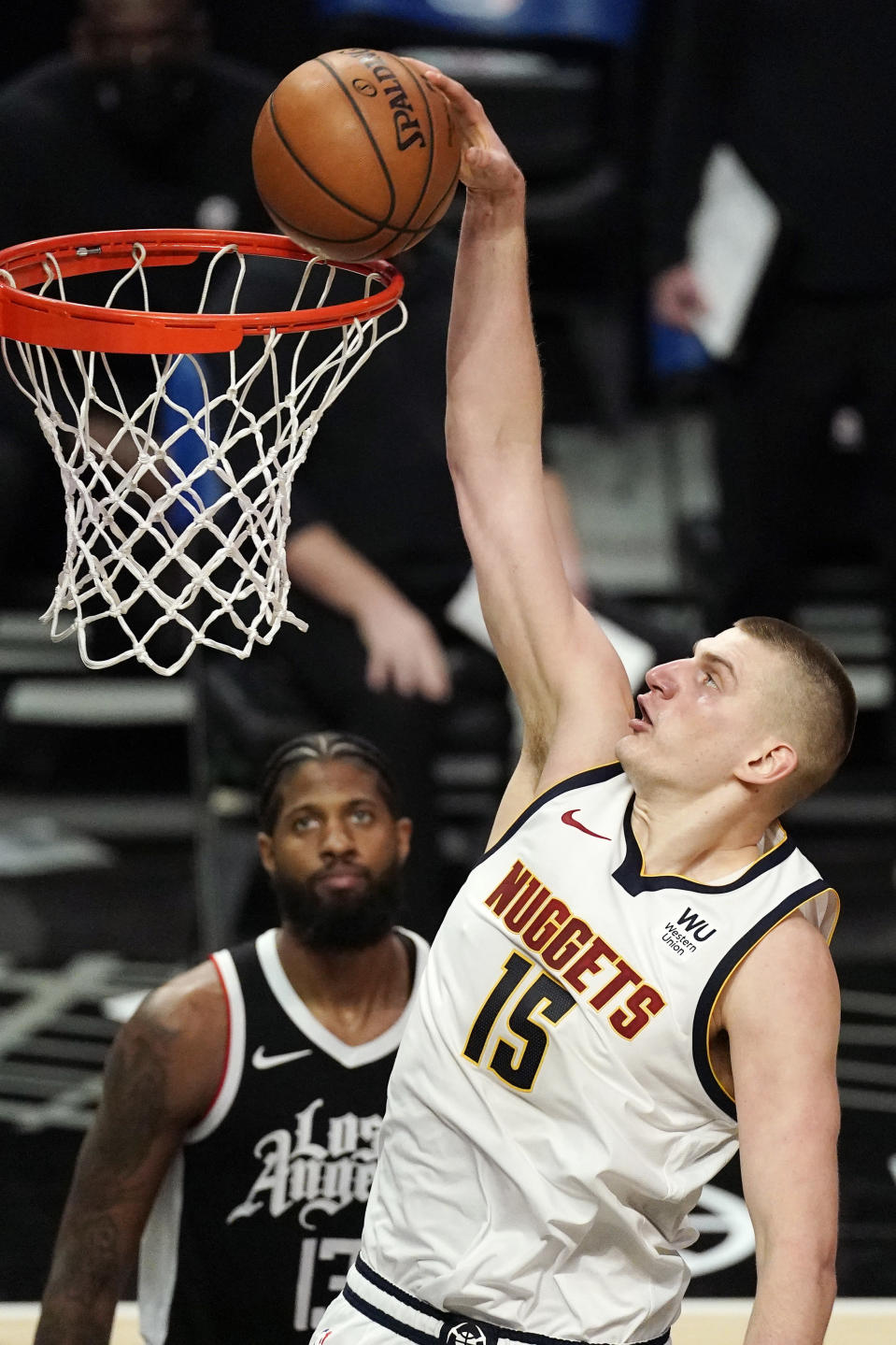 Denver Nuggets center Nikola Jokic, right, dunks as Los Angeles Clippers guard Paul George watches during the second half of an NBA basketball game Saturday, May 1, 2021, in Los Angeles. (AP Photo/Mark J. Terrill)