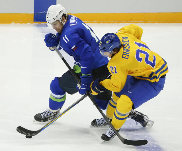 Slovenia forward Anze Kopitar, left, and Sweden forward Loui Eriksson battle for the puck in the second period of a men's ice hockey game at the 2014 Winter Olympics, Wednesday, Feb. 19, 2014, in Sochi, Russia. (AP Photo/Mark Humphrey)