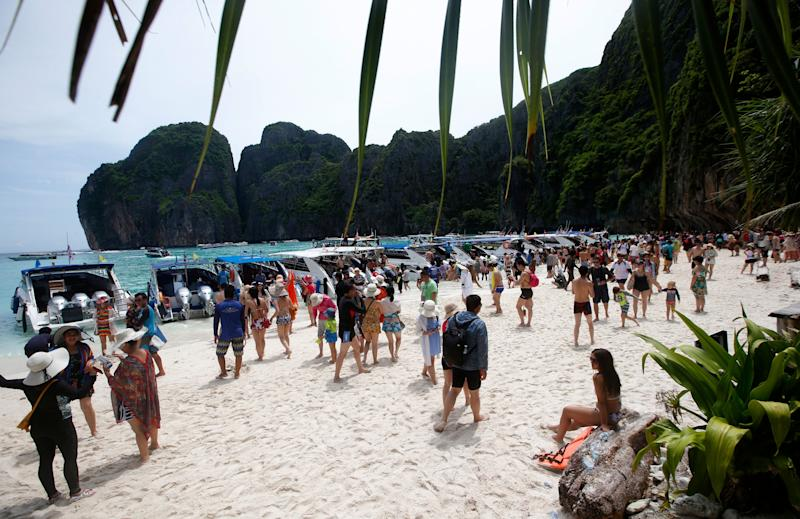 In this photo taken Thursday, May 31, 2018, tourists enjoy the beach on Maya Bay, Phi Phi Leh island in Krabi province, Thailand. Maya Bay will close to tourists indefinitely until its ecosystem returns to its full condition, the Department of National Parks, Wildlife and Plant Conservation said in a Monday announcement published on the Royal Gazette. (AP Photo/Sakchai Lalit)