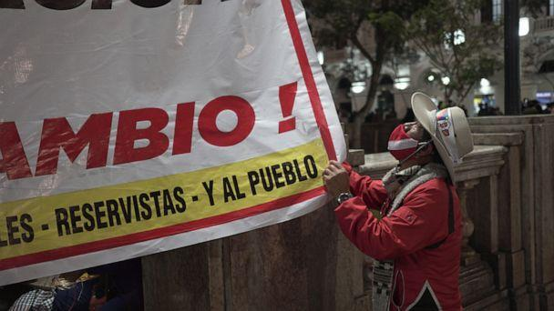PHOTO: A supporter of Peru's far-left candidate Pedro Castillo, looks up at a sign in support as they converged on the capital to protest allegations of fraud by his opponent Keiko Fujimori. (Neil Giardino/ABC News)