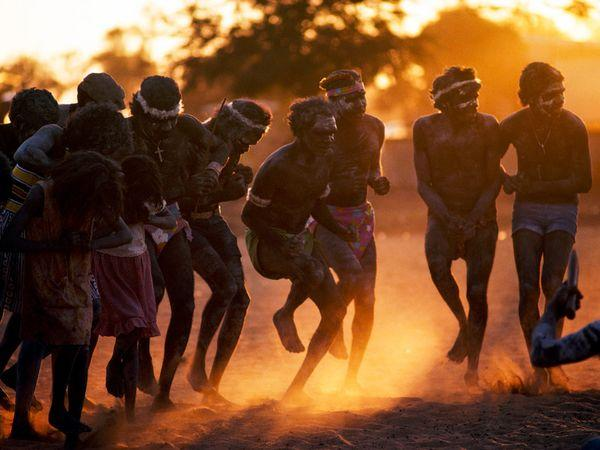 Aborigines kick up dust in a dance at sunset. The original inhabitants of Australia, Aborigines were there for more than 40,000 years before white men arrived. European settlers brought disease and politics to the continent, severely endangering the Aborigines' distinct culture, language, and lifestyle.