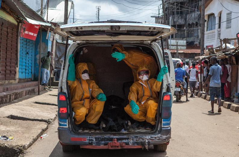 Volunteers arrive to pick up bodies of people who died of the Ebola virus, on October 8, 2014 in Freetown